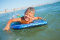 Boy has fun with the surfboard on in transparency sea Royalty Free Stock Photography