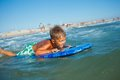Boy has fun with the surfboard on in transparency sea Stock Image