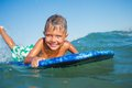 Boy has fun with the surfboard on in transparency sea Royalty Free Stock Photos