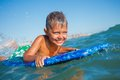 Boy has fun with the surfboard on in transparency sea Royalty Free Stock Images