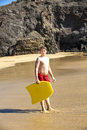 Boy has fun surfing in the waves at beautiful beach Royalty Free Stock Images