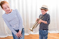 Boy with hat is playing the trumpet - sister annoyed Royalty Free Stock Photo