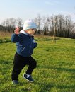 Boy having fun outdoors while performing his first few steps on a sunny day at the garden Royalty Free Stock Photography