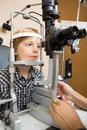 Boy having his eyes examined with slit lamp by preadolescent doctor Royalty Free Stock Photos