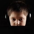Boy in headphones behind laptop darkness Stock Images