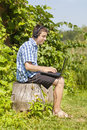 Boy with headphones mic and pc in garden Royalty Free Stock Photo