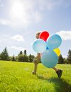 Boy with helium balloons walking in park full length side view of young colorful Stock Images