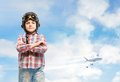 Boy in helmet pilot stands with his arms crossed in the clouds dreaming of becoming a pilot Stock Image