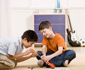 Boy helping friend fix broken toy Stock Photography