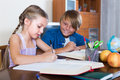 Boy helping his little sister to do homework with books indoors Stock Images
