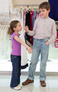 The boy helps girl to choose clothes in shop of childrens clothing Stock Images