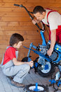 Boy helps his father mounting a cultivator machine tiller head on Stock Photography