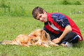 Boy with his dog on the grass teen stroking sitting Stock Photo