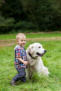 Boy and his dog months old with golden retriever at park Stock Photography