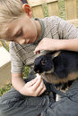 Boy with his first pet blond youngster and best friend playing outdoors and snuggling huddling up a cute black dwarf rabbit Stock Image