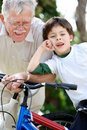 Boy and his grandfather standing with bicycle Stock Photo