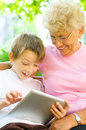 Boy with his grandmother using tablet little pc sitting in the park Royalty Free Stock Images