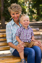Boy with his mother sitting on the bench little blond banch Royalty Free Stock Photo