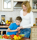 Boy with his pregnant mother in the kitchen Stock Image