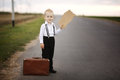 Boy hitch hiking at road holding cardboard Royalty Free Stock Image