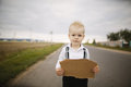 Boy hitch hiking at road holding cardboard Royalty Free Stock Photo