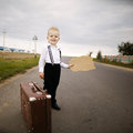 Boy hitch hiking at road holding cardboard Royalty Free Stock Photography