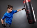 Boy hitting the punching bag on gray background Royalty Free Stock Photography