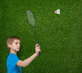 Boy holding badminton racket flying shuttlecock happy and over green grass Royalty Free Stock Photography
