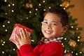 Boy Holding Christmas Present In Front Of Tree Stock Photo