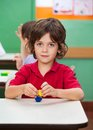 Boy holding clay model at desk cute little in classroom Stock Photography