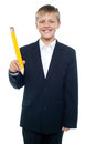 Boy holding giant sized yellow pencil Stock Photos