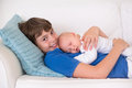 Boy holding his newborn baby brother happy laughing sleeping siblings with big age difference children playing at home on a white Stock Photos