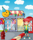 A boy holding a lollipop outside the party shop