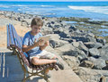 Boy holding looking tablet pc sea side Stock Image
