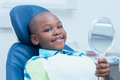 Boy holding at mirror in the dentists chair Royalty Free Stock Photo
