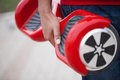 Boy holding modern red electric mini segway or hover board scooter Royalty Free Stock Photo