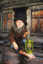 The boy is holding an old kerosene lamp in his hands. Stylized retro portrait Royalty Free Stock Photo