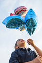 Boy holding patriotic flag balloons close up of looking up while red white and blue Stock Photos