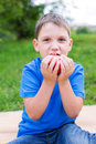Boy holding red apple by two hands and nibbling selective focus Royalty Free Stock Photos