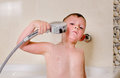 Boy holding shower over his head bathing in the bathroom Royalty Free Stock Photo