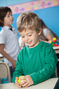 Boy holding smith apple happy cute with classmate in background at kindergarten Royalty Free Stock Photos