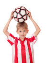 Boy holding a soccer ball above his head Stock Photo