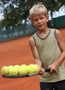 Boy holding tennis racket with balls Stock Image