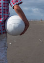 Boy holding volleyball on beach Stock Photos