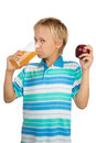 Boy holds a glass with an apple juice with one hand and apple i school aged is holding in red in another Royalty Free Stock Images