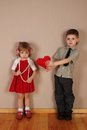 Boy holds red heart for girl Stock Photography