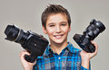 Boy holds the two photo cameras smiling caucasian with dslr camera posing at studio over grey background Royalty Free Stock Photo