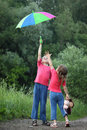 Boy holds umbrella over head, girl pulls to Stock Images