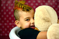 Boy hugging teddybear and smiling Royalty Free Stock Photo