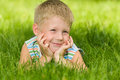 Boy imagines on the green grass a thoughtful in striped shirt is lying in summer Stock Image